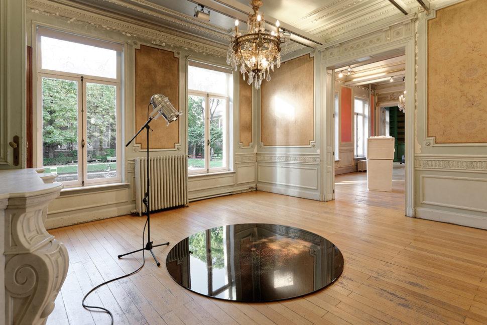 Jonathan Sullam, Champagne taste lemonade money, 2015, Aluminum black coated disk, holographic powder and light projector, 200 x 200 cm, Maison des Arts de Schaerbeek (BE)